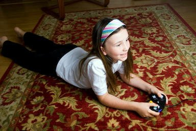 girl plays video games on area rug recently cleaned by Temecula Valley Chem-Dry