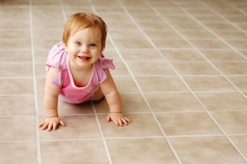 clean tile with a baby crawling on it